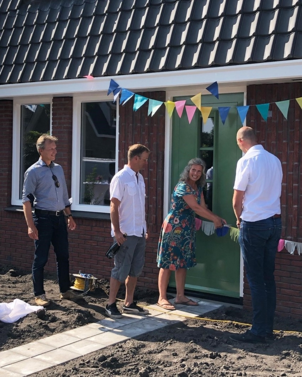 Levinus Jongmans van gemeente Zaanstad (links) en Jacob Prins van bouwbedrijf Van Der Gragt (rechts) begeleiden de trotse bewoners (midden) naar hun nieuwe, duurzame woning.  (Foto: aangeleverd) © rodi