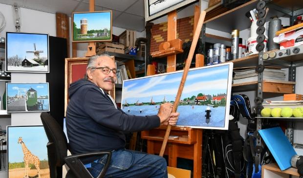 <p>Henk Deyle legt de laatste hand aan zijn laatste werk: een op eikenhout geschilderde voorstelling van de Zaan en Zaanse Schans. </p>