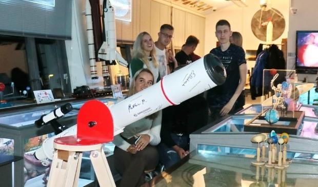 <p>Jan Ruers rijkt telescoop uit aan Don Bosco college.</p>