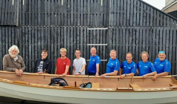 <p>Leerlingen en docenten van Scholen aan Zee met een door henzelf gebouwde St Ayles Skiff. Geheel links Bert van Baar.</p>