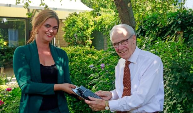<p>Theo Leuven (86) uit Landsmeer ontvangt de omvormer van Agiba Solar.</p>