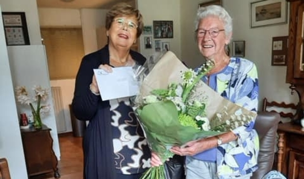 <p>Mevrouw Van Beek straalt als ze een bosje bloemen krijgt van de burgemeester.</p>