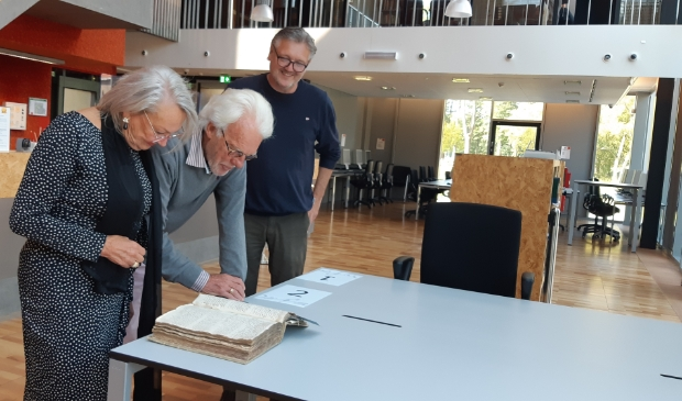 <p>Paul Rietmeijer en Ytje Visser bekijken samen met Peter Swart (r) een zeventiende-eeuws belastingregister. </p>
