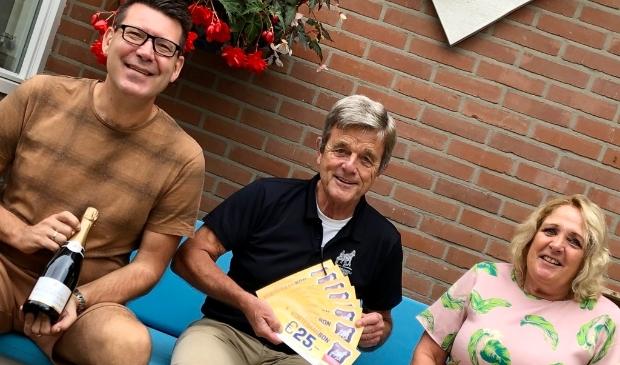 <p>Het echtpaar Jansen krijgt de hoofdprijs uit handen van secretaris Hans Nelissen (m.) van de harddraverijvereniging.</p>