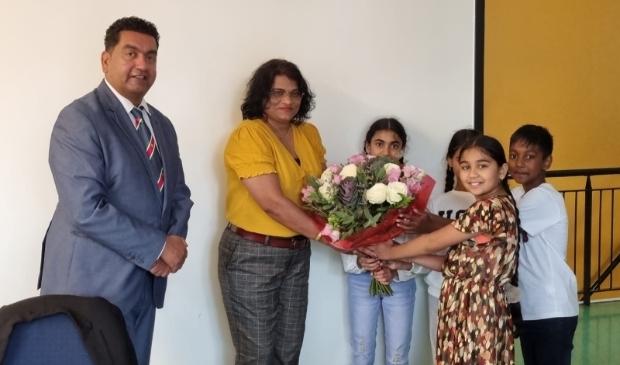 <p>Senrita Gobardhan krijgt een bos bloemen van enkele leerlingen van SVS. Links is Rajesh Ramnewash.&nbsp;</p>