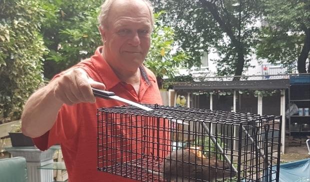 <p>René Oudshoorn met een rat in een val. Het probleem wordt volgens hem onvoldoende aangepakt.</p>