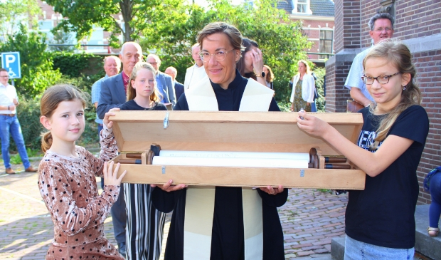 <p>Predikante Anne-Marie van Briemen begeleidt Linn (li) en Menthe bij het overdragen van de dooprollen, van de Zijdekerk naar de Dorpskerk.</p>