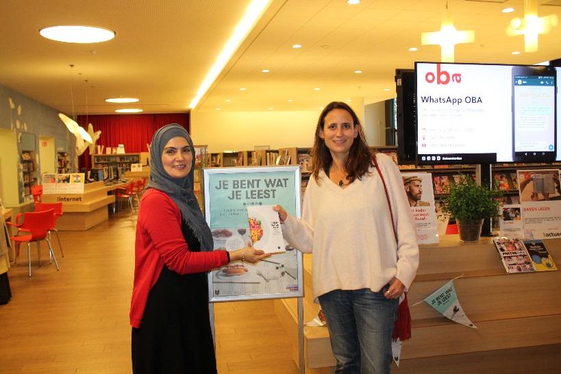 Meliha Koyluoglu overhandigt het boek aan Fiona Remp. (Foto: Hillery - OBA Banne)