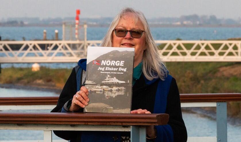 Cora de Boed met haar boek. Achter haar het Haringvliet. Foto: Leendert Verkerke