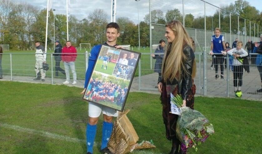 Jubilaris Tim Mackloet ontving een fotocollage. links van hem zijn vriendin Rianne van Meurs.