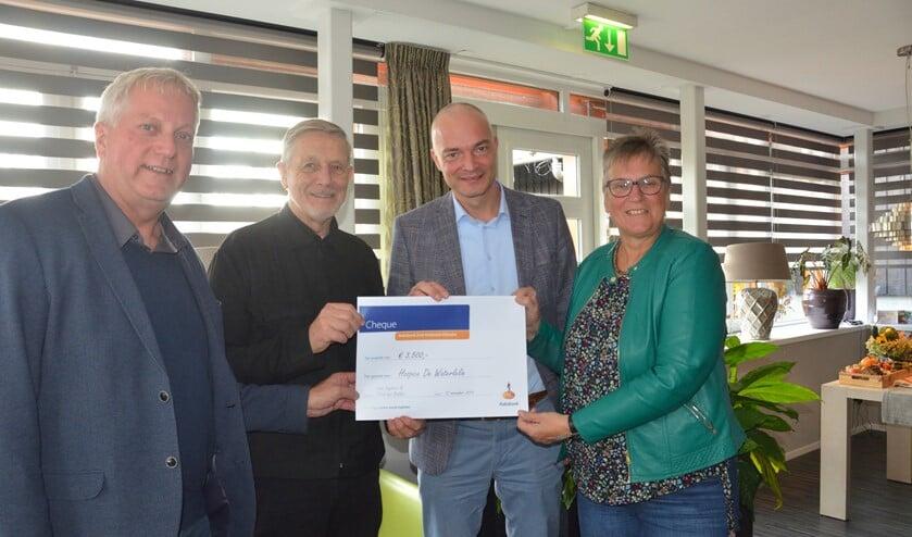Jacob den Bakker (links) en Cees Engbers (2e van rechts) overhandigen de cheque aan vertegenwoordigers van De Waterlelie.