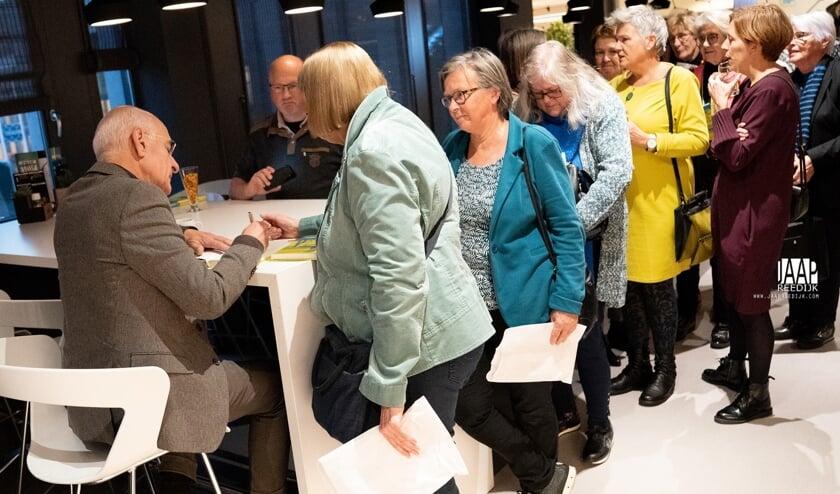 Frits Spits signeert zijn boek.