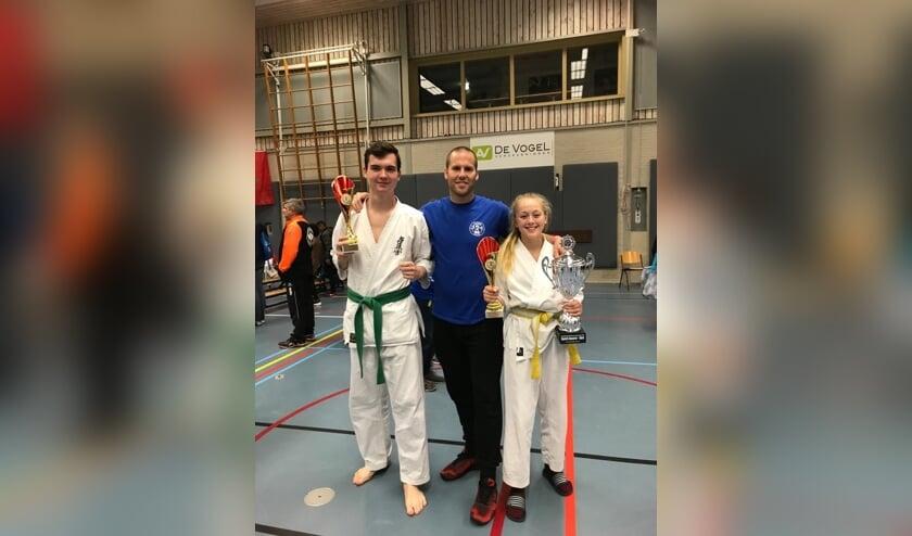 Bas van Brussel (links) en Jette Prins (rechts) met hun gewonnen beker met in hun midden trainer Jacques van Roosmalen.
