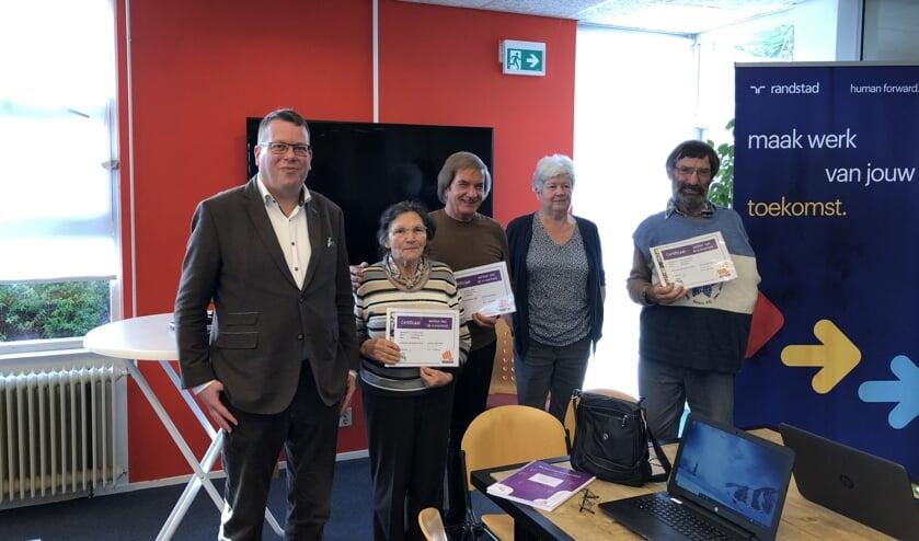 Drie van de acht cursisten met hun welverdiende certificaat. Naast hen wethouder Bruggeman en docente Harmke Spoelman.