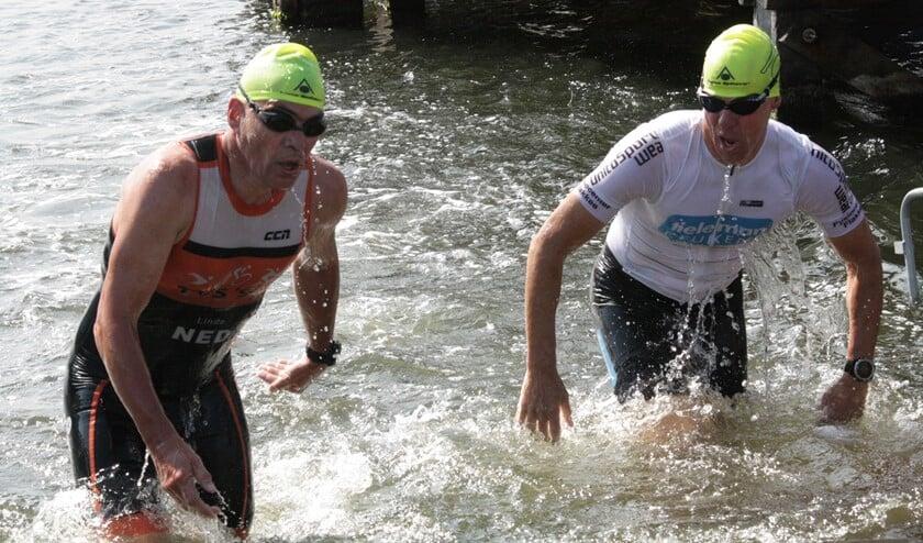 Nico Paasse (rechts) als één van de eerste uit het water na 1000 meter zwemmen. (Foto Fred Götzenberger)