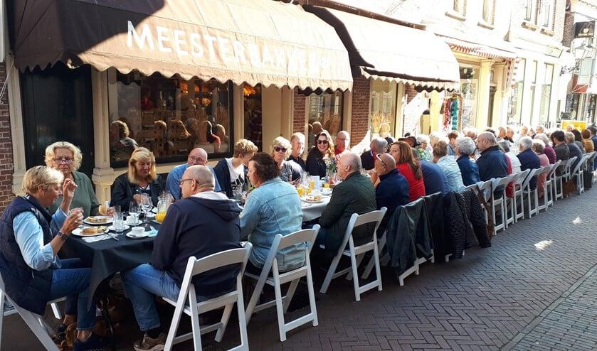 Met zijn allen gezellig aan een lange tafel in de zon!