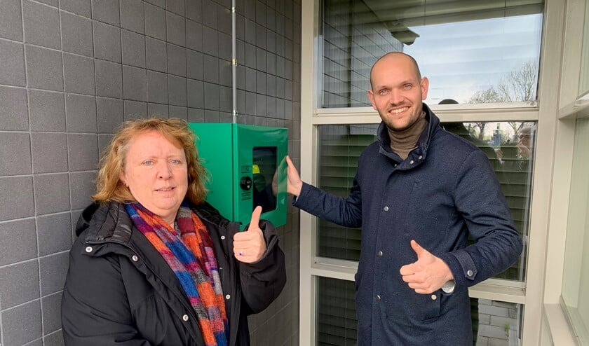Anja van der Sijde (De Zes Kernen) en wethouder Struijk bij de AED in Abbenbroek.