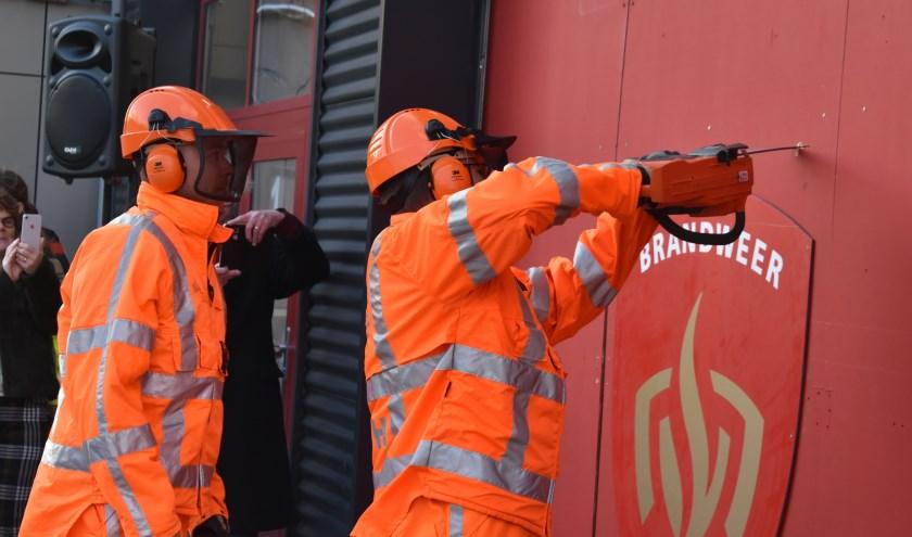 Burgemeester Arends maakte met behulp van een kettingzaag vakkundig eengat in een houten voorportaal van de nieuwe tijdelijke brandweerkazerne Naaldwijk.