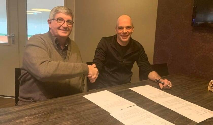 Voorzitter Jan de Leeuw (links) en Petri van Dijk bevestigen de verlenging met een handdruk. Van Dijk blijft nog een seizoen bij  Good Luck.