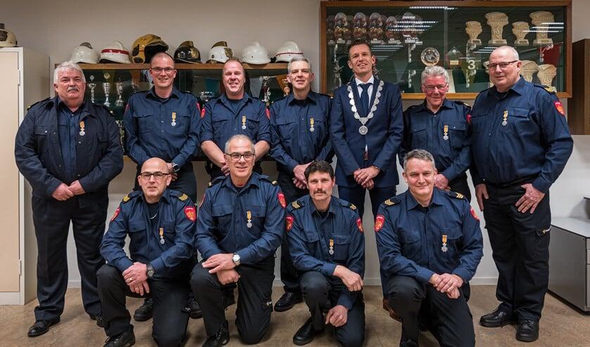 Locoburgemeester Daan Markwat speldde  in Dirksland bij tien brandweerlieden een Koninklijke onderscheiding op.
