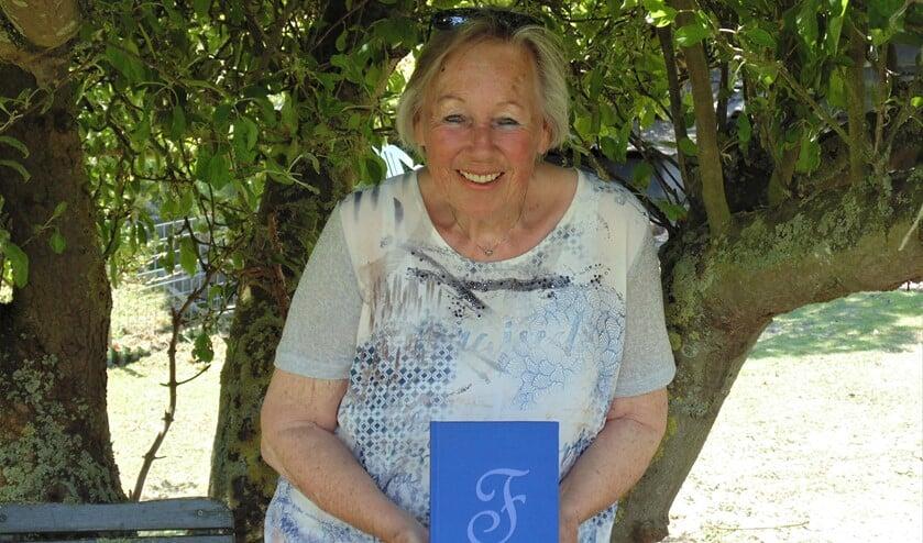 Frouke Bienefelt met haar gedichtenbundel in haar tuin. (Foto: Cora de Boed)