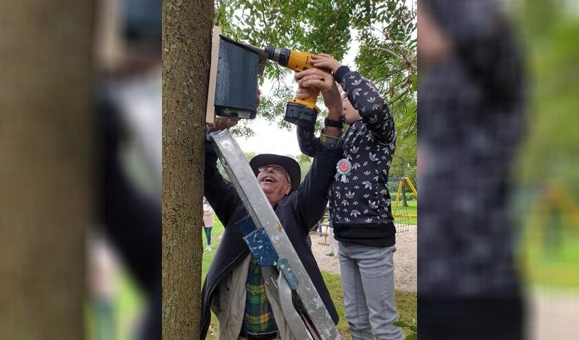 Djévano  mocht meneer Wim helpen bij het ophangen van het vogelhuisje.