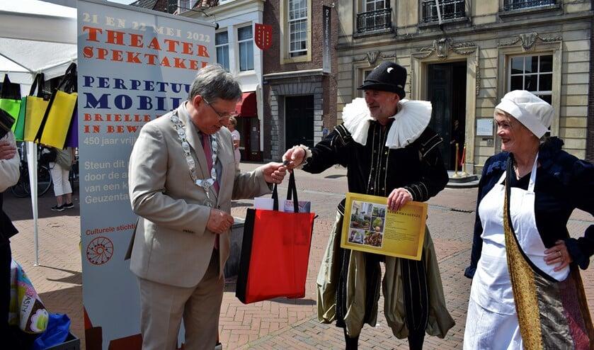 <p>Willem van Oranje overhandigt Burgemeester Rensen, onder toeziend oog van visvrouw Kaat, de Geuzentas</p>