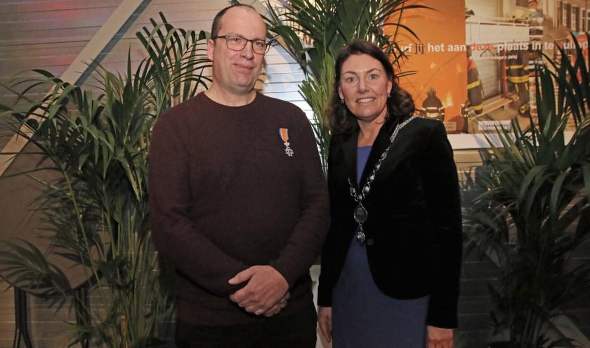 Brandweerman Mart Potter met zijn lintje en burgemeester Van Egmond met haar nieuwe ambtsketen. FOTO COBY WEIJERS