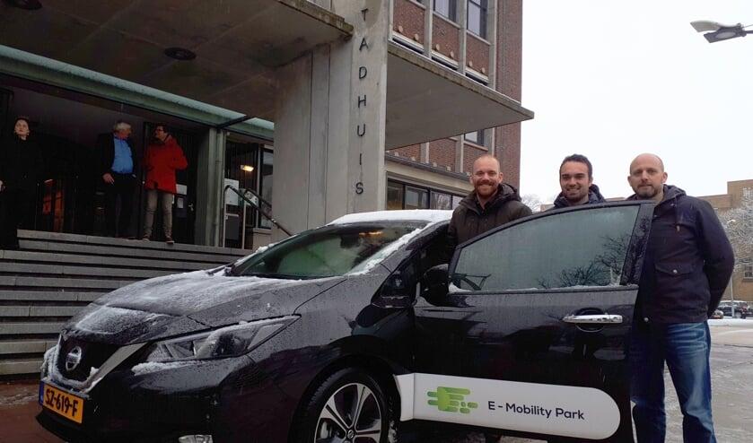Wethouder Sem Stroosnijder en David Tolhoek en Sjoerd de Jong (vlnr) van de stichting bij de elektrische deelauto.