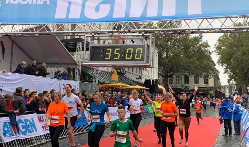 De deelnemers komen vol blijdschap over de finish.