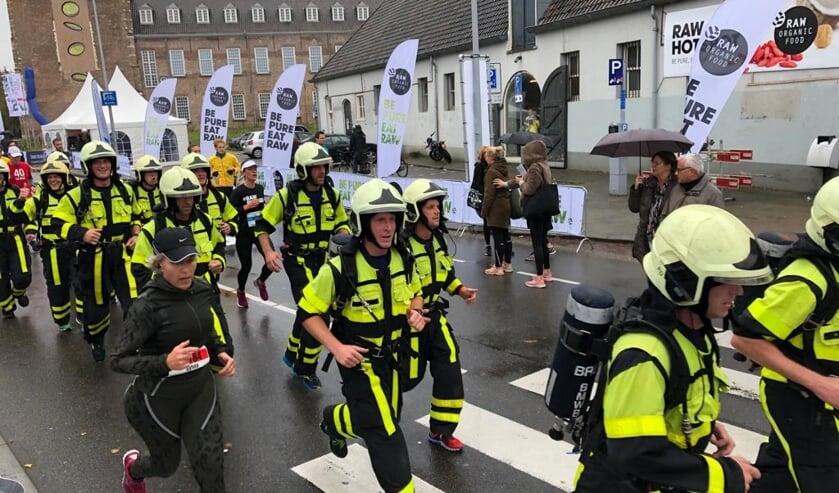 De brandweer mannen rennen in uitrusting van vijftien kilo.
