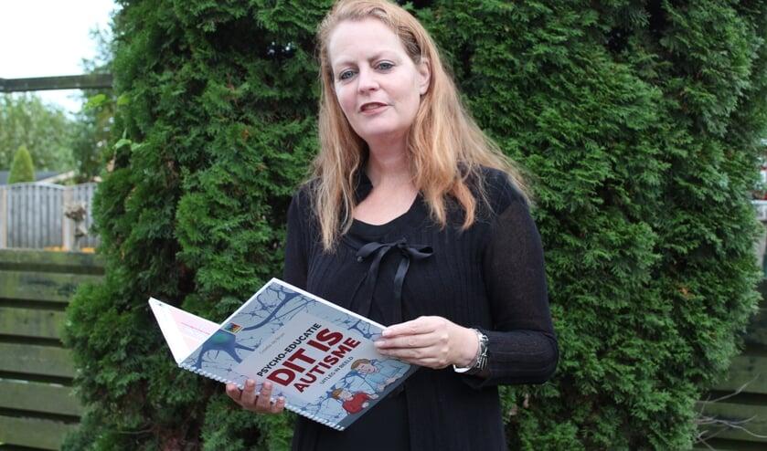 Noor van Oers houdt het nieuwe boek 'Dit is Autisme' vast met een uitleg in beeld.