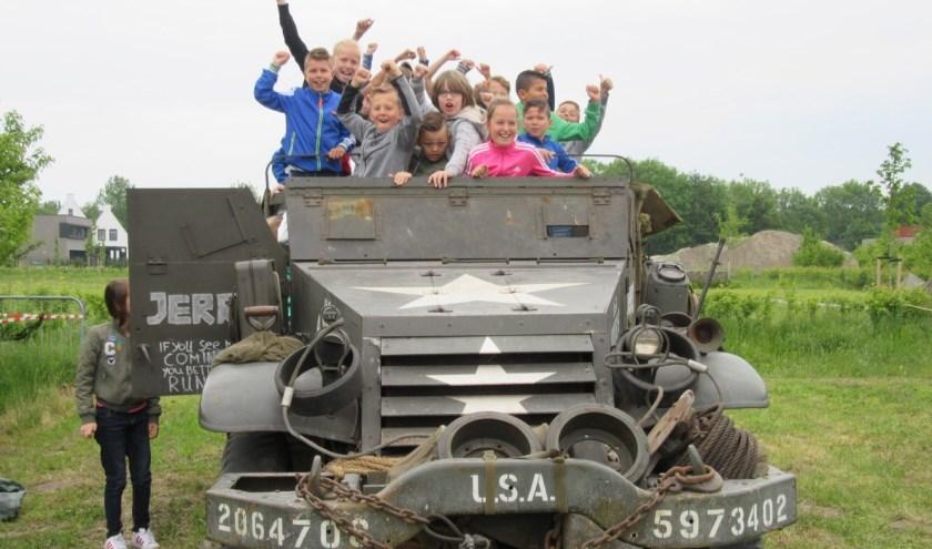 Kapelse kinderen bij een legervoertuig van museum Vitality.