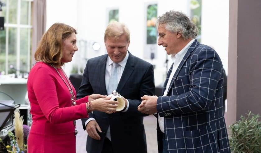 Burgemeester José van Egmond overhandigt het predicaat aan eigenaren Geert Jan Vogels en Ward Schröder van Van Doorn Dakspecialist.