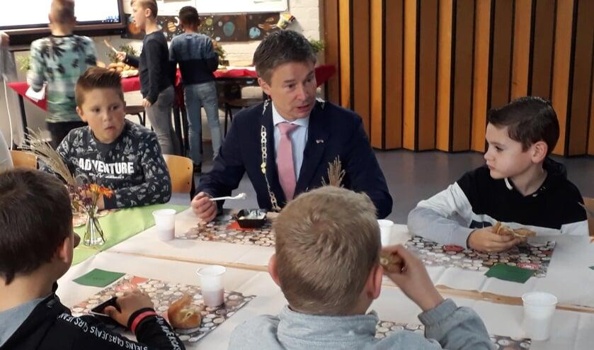 Leerlingen van De Hoeksteen eten en kletsen met burgemeester Hieltjes.