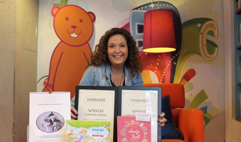 Vivianne de Caluwé met haar boeken en teddyberen kalender in bibliotheek Het Markiezaat Steenbergen.