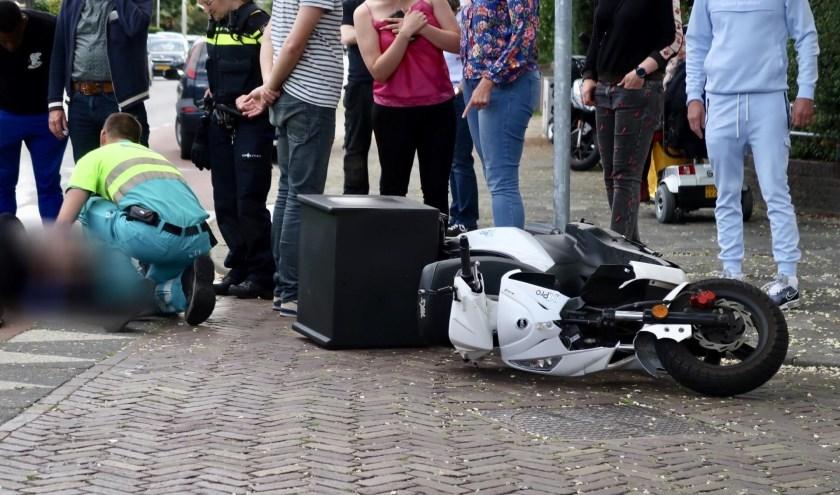 De scooter viel door de botsing op de grond.
