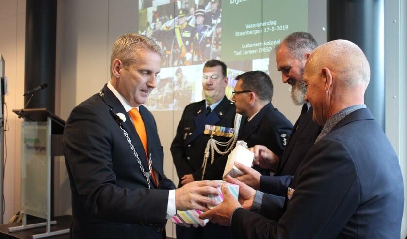 Burgemeester Van den Belt deelt een glasgeschenk uit aan bestuursleden van Veteranen Steenbergen (VEST)