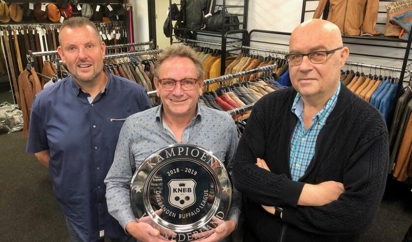 Ad Braspenning van L&B Ledermode met de kampioensschaal, links Gerwin Valentijn, rechts Kees Broos. FOTO JOHAN WAGENMAKERS