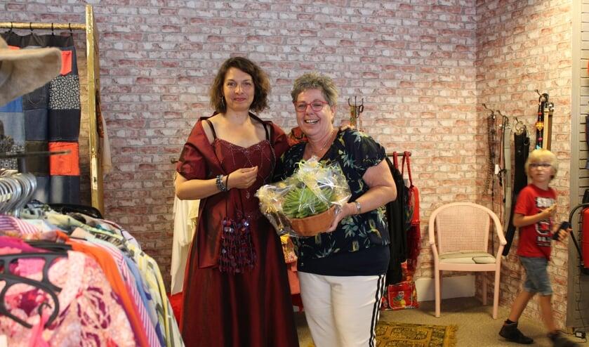 Marina Fidder van gemeente Steenbergen past een galajurk in De Ontmoetingswinkel van Rian Liefhebber.
