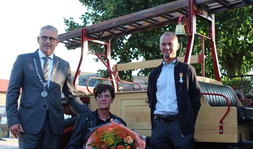 Burgemeester Van den Belt eert brandweerman Jack Jacobs met een lintje op de kazerne in Kruisland.