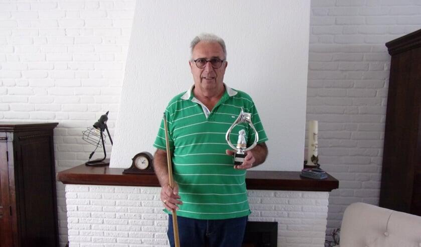 Competitieleider Henk van Zunderd van de Laatbloeiers met biljartkeu en een poedelprijs die hij ooit won. FOTO MARILYN PIETERSZ
