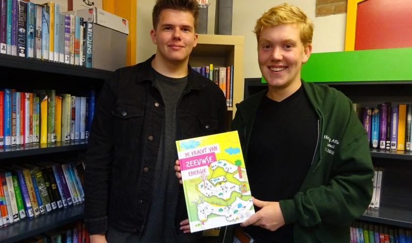 Bjorn de Nooijer (l) en Arjan van Dorsselaer lezen voor uit 'De kracht van Zeeuwse energie'. FOTO MARIELJA TEN BRUGGENCATE