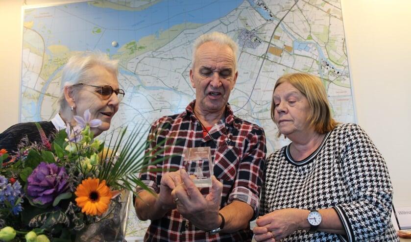 Oud-molenaar Lodi Baauw kijkt naar de glassculptuur, samen met zijn vrouw, die hij van wethouders Baartmans kreeg.