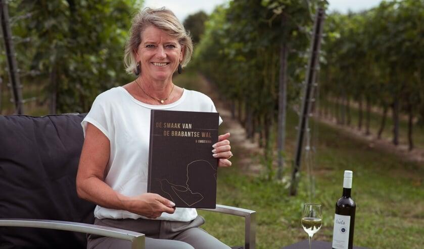 <p>Margot Haest met haar boek in de wijngaard van Domaine De Brabantse Wal FOTO GIJS PROOST FOTOGRAFIE</p>