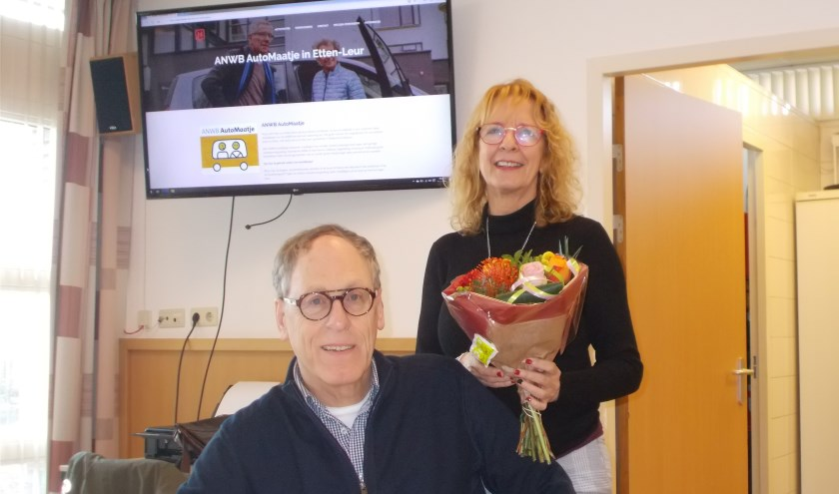 Jaap Lucieer overhandigt coördinator Els de Lange van AutoMaatje bloemen.