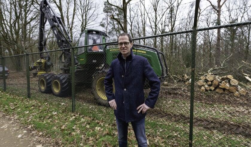 Wethouder Martien de Bruijn met de kapwerkzaamheden op de achtergrond.