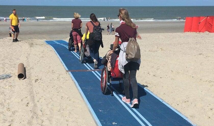 Een mobi-mat helpt rolstoelers het strand op.