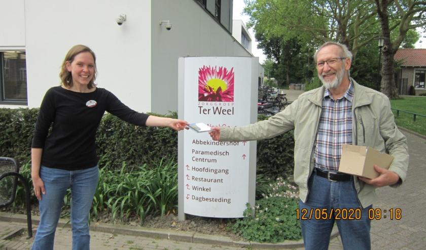 Arie van Kralingen overhandigt de Zeeuws Mannenkoor CD aan Suzanne Bassie van Ter Weel.