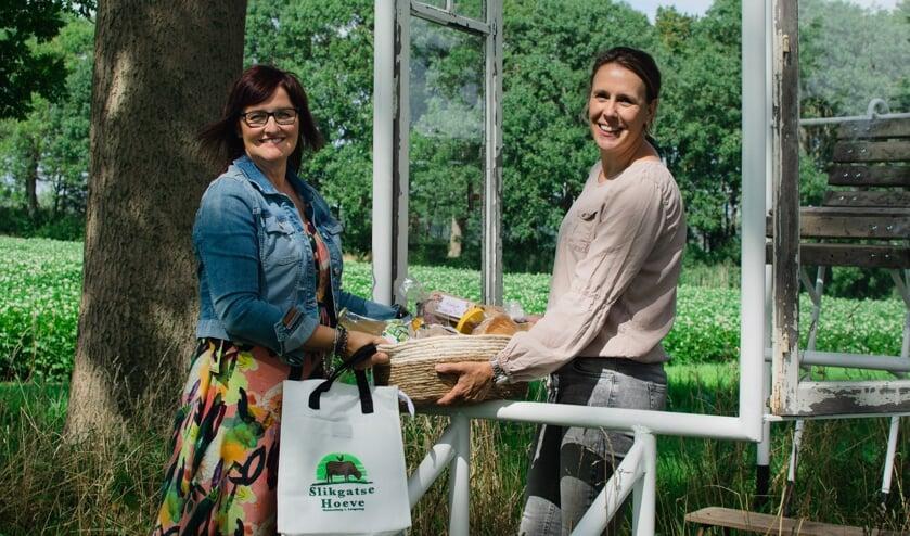 Leontine Ouwerling (rechts) ontvangt een streekproductenpakket uit handen van Petra Wevers van KrachtigBuiten.